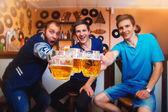 Tre bicchieri di tintinnio uomo allegro di birra in un bar