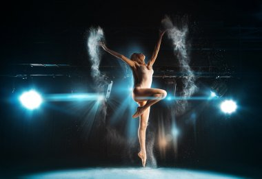 Wonderful adult ballerina posing on stage against spotlights