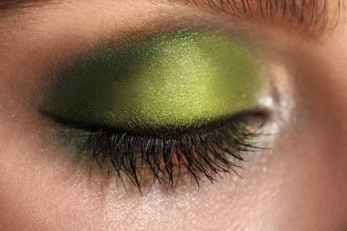 macro picture of closed eye with green colors makeup