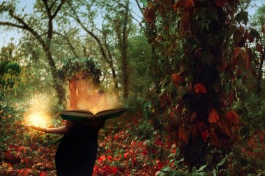 fantastic young witch conjures by a magical book in the woods