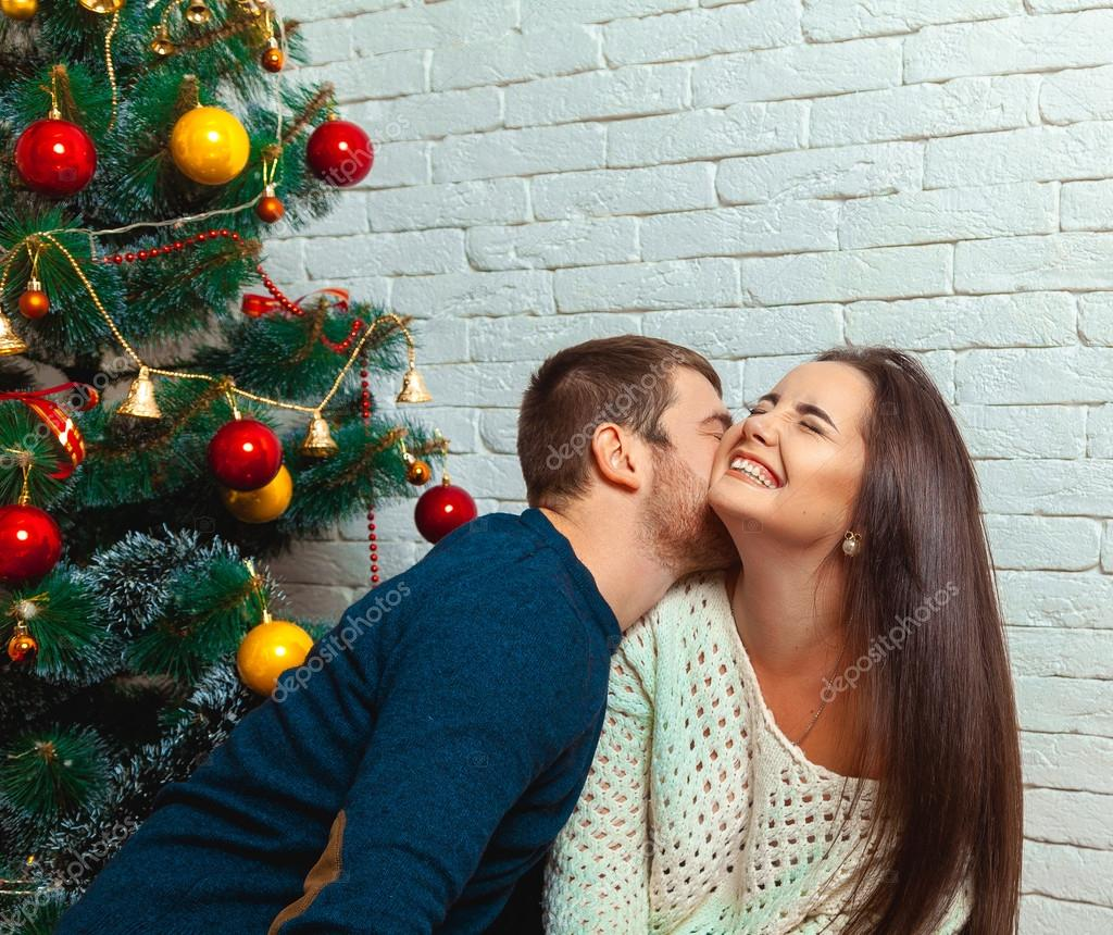 guy kisses a girl under the tree on Christmas