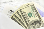 Tax forms with dollar bills