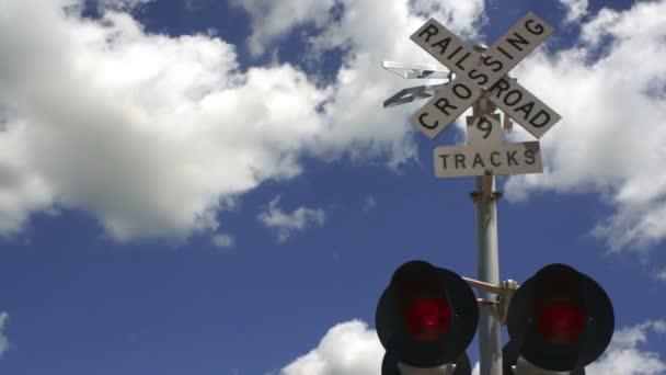 Železniční vlak přes červených výstražných světel bliká mraky modrá obloha