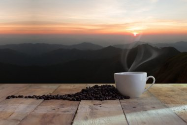 cup of black coffee and beans over wood table and Sunset