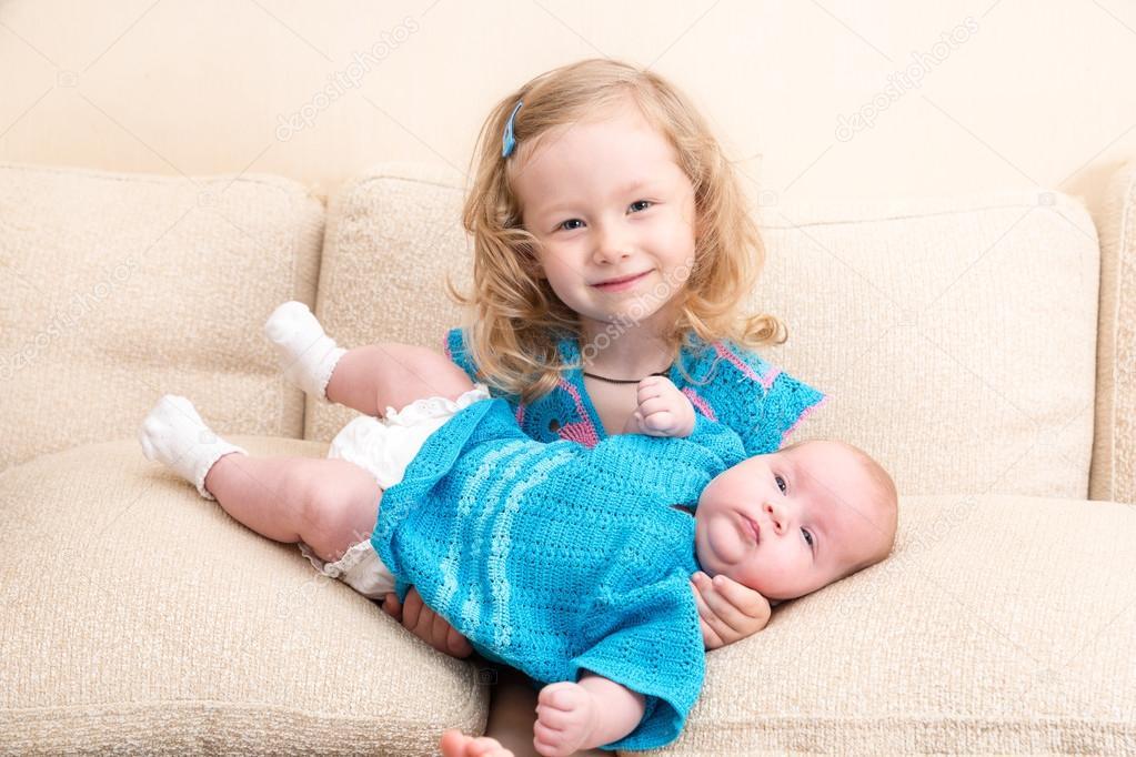 4fc9ea51c276e Zwei Schwestern. Ältere Schwester Kind umarmt sein neugeborenes  Schwesterchen. Süße Kinder Mädchen auf Bett