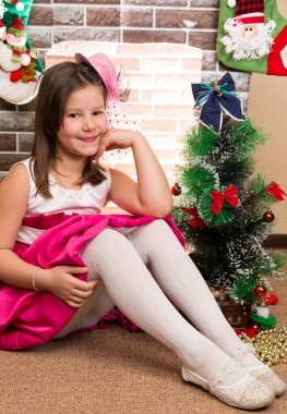 Beautiful girl in ball dress by fireplace. Christmas and New Year