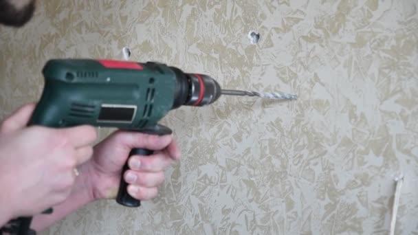Menschenhände arbeiten mit Bohrwerkzeug, um Loch in Wand zu machen. Heimwerker. Zeitlupe