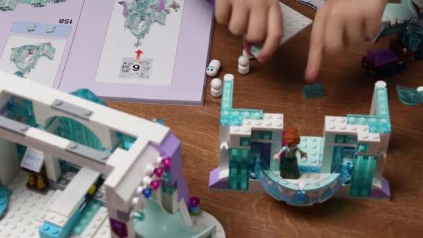 Batole ruka dává hračky Lego bloky na stůl a hraje zmrazené Disney hrad