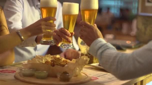 Přátel cinká sklenice pivo v baru