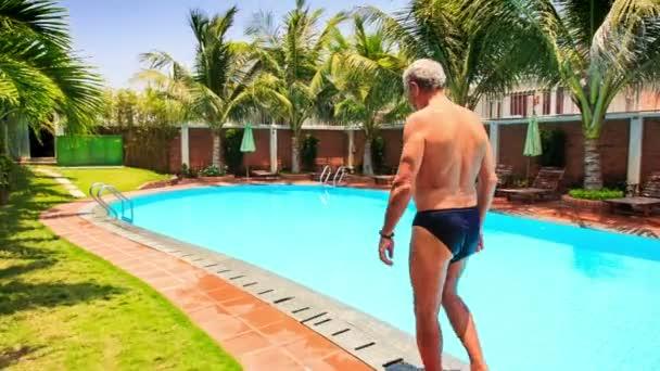 Man Walks along Swimming Pool