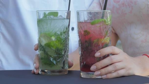 Frauenhände halten und heben Cocktailgläser im Restaurant