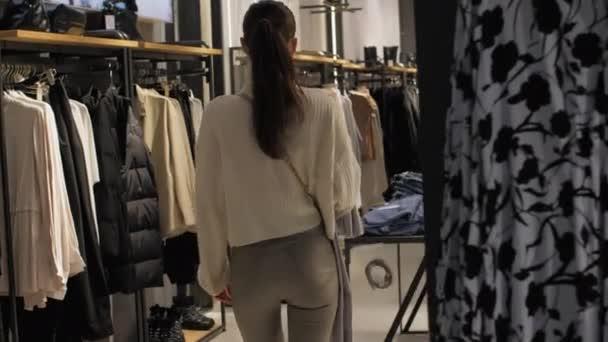 Bruneta kráčí po obchodě a dívá se na různé oblečení