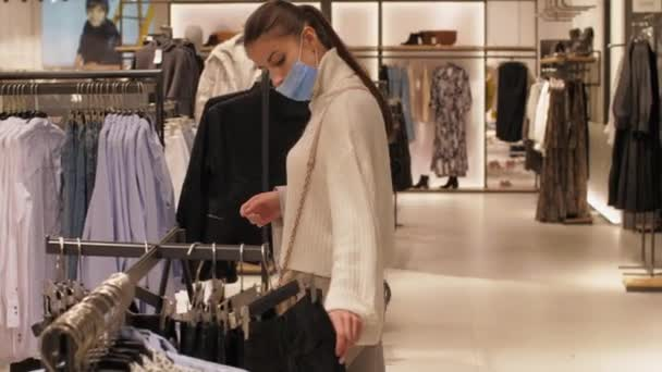 Mladá žena v modré jednorázové masky kráčí podél oblečení shop