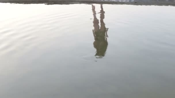 primitive Frau im Spiegelbild des Flusses