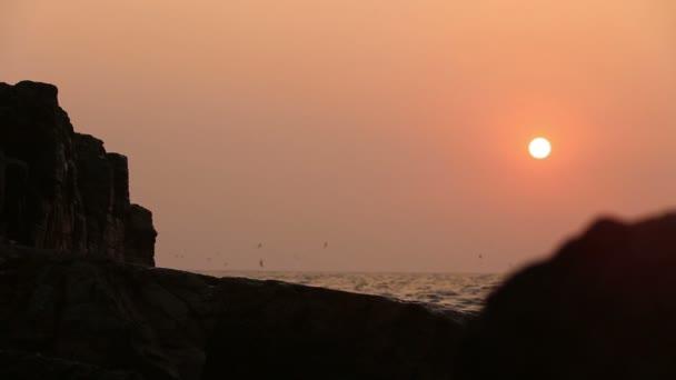 skála v moři při západu slunce