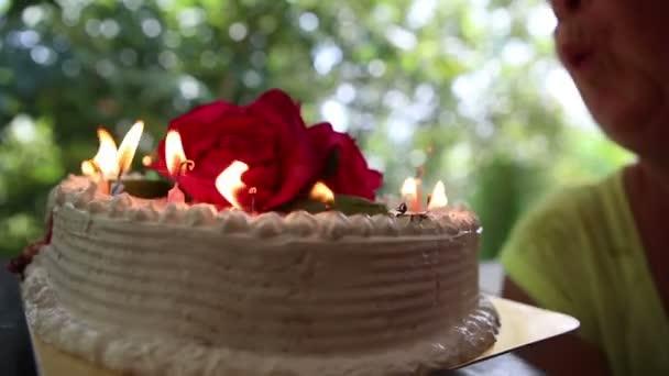 Žena foukání svíčky na dort