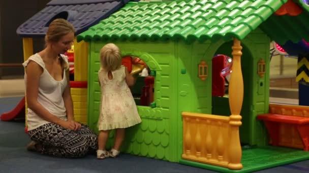 Dítě hrající s matkou v domě hraček