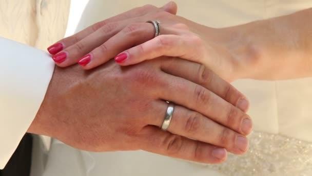 Mani dello sposo e della sposa con gli anelli di nozze