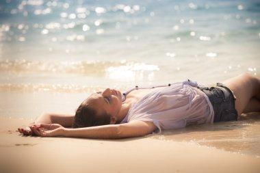 Sexy girl laying on sea beach