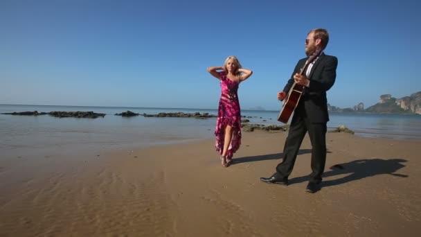 Nő és férfi a gitár a beach