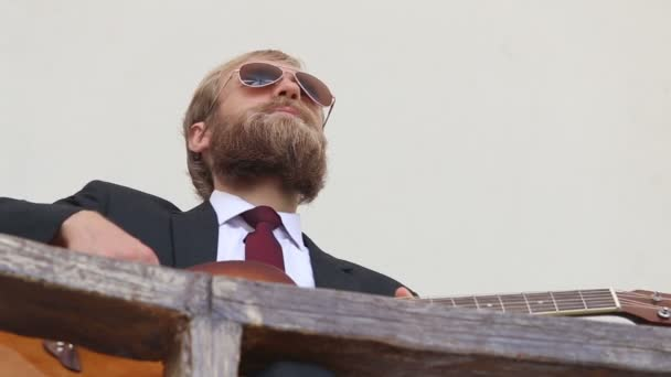 Bearded man in suit and glasses with guitar