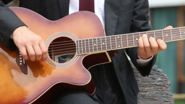man in suit and glasses plays guitar