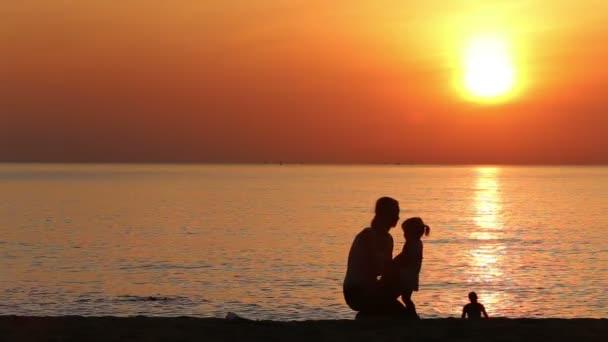 Mutter und Tochter umarmen sich am Strand