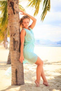 Blonde girl in azure looks  on beach
