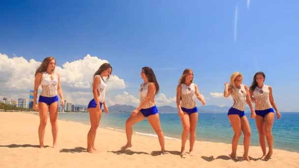 squad of cute cheerleaders on beach