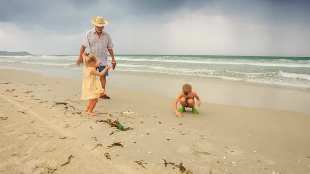 grandfather with boy and girl on beach