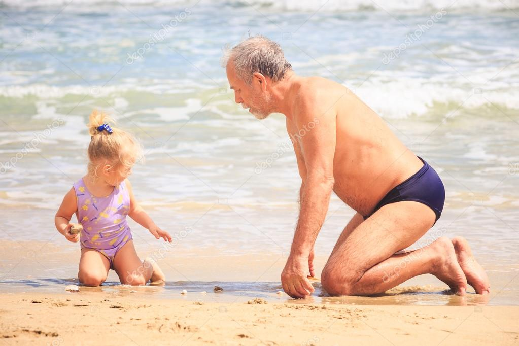Bearded grandfather, little blond girl with pigtail sit on wet sand beach  look at nice shell at wave surf — Photo by smoliakov