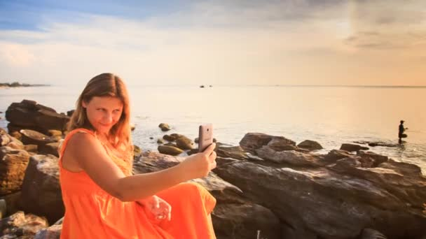 woman taking selfie over sunset coast