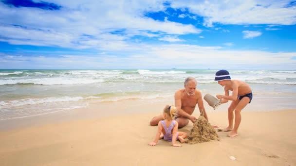 Großvater mit jungen und Mädchen am Strand