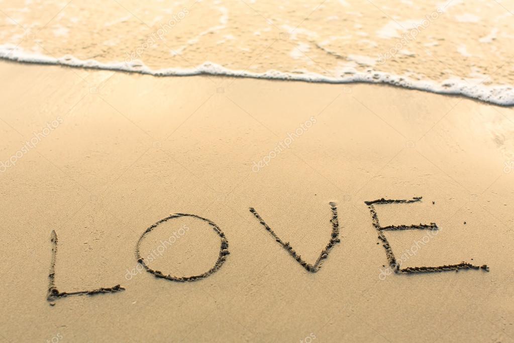 Love - written on texture of sea sand.