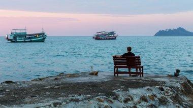 man sitting on sea pier
