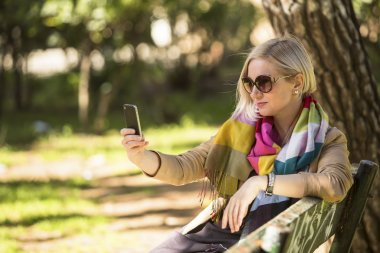 Blonde woman doing a self-portrait with smartphone