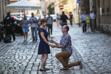 Man on knees gives a woman a flower