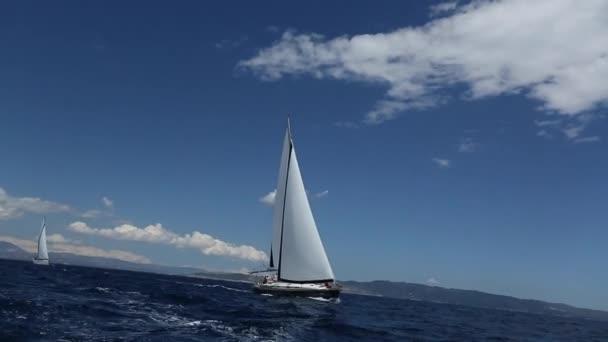 Loď jachty s bílými plachtami na otevřeném moři. Luxusní lodě. Plachtění.