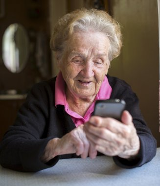 Elderly woman typing on smartphone
