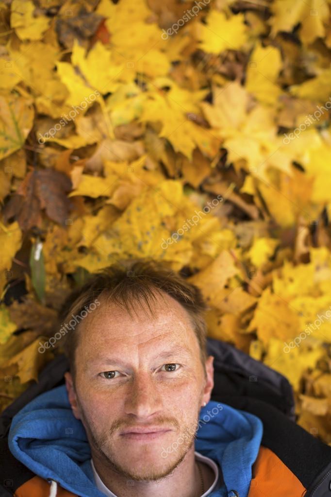 Man lying on autumn leaves.