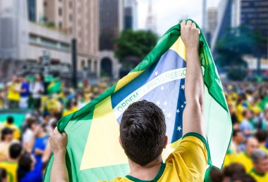 man holding the flag of Brazil