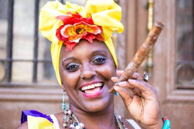 Portrait of african cuban woman smoking cigar and looking at camera smiling