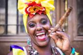 Fotografie Portrait of african cuban woman smoking cigar and smiling
