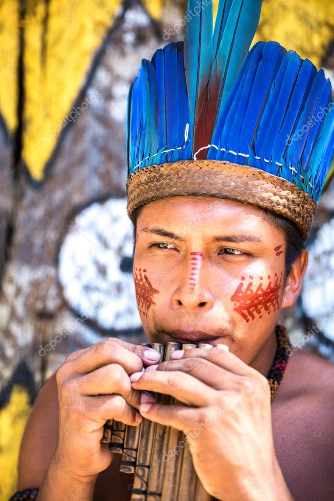 Native Brazilian playing wooden flute at an indigenous tribe in the Amazon