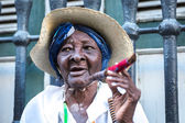 Portrait of african cuban woman smoking cigar in Havana, Cuba.