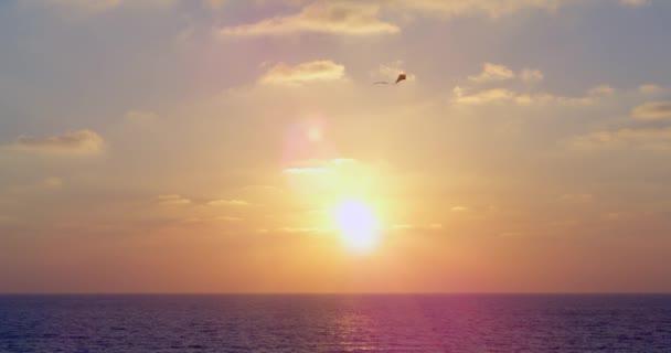 Krásné středomořské slunce, modré vlny a žluto růžová slunce. Na obloze letí trojúhelníkový drak