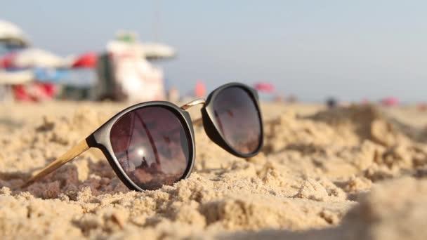 Body ležící na písku. V sluneční brýle odráží slunce, oblohy a lidské