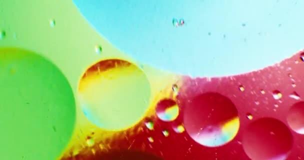 Lubrifichi le gocce che galleggia in acqua sopra un sotterraneo colorato con effetto pittura ad olio. Girato su colore rosso