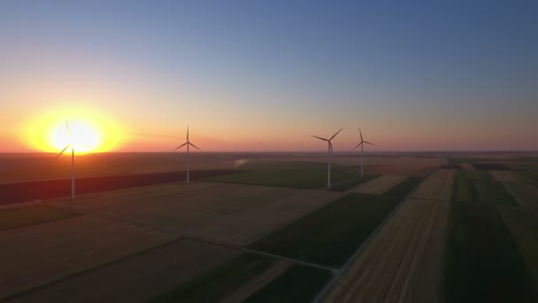 Aerial footage of wind turbines in a field at sunset. Wind turbines producing clean renewable energy.