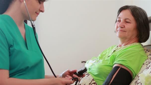 Zdravotní sestra, kontrola krevního tlaku na starší žena